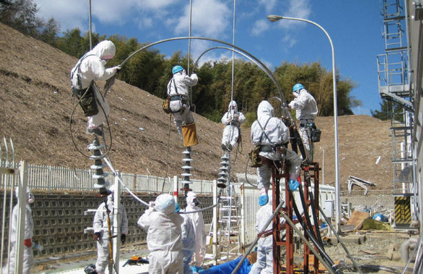 Tokyo Electric Power Company (TEPCO)employees wear protective gear as they work near the Fukushima Dai-ichi (no.1) nuclear power plant on March 18, 2011.